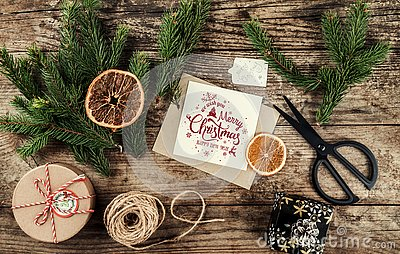 Merry Christmas card with fir branches, gifts on wooden background with scissors and skein of jute. Xmas and Happy New Year theme,
