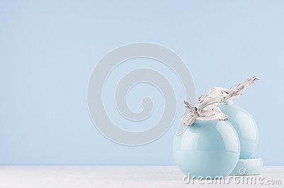Japanese style in home decor - shabby old grey branch and glossy ceramic spheres on white light shelf and blue wall.