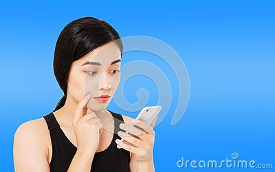 Korean,asian woman reads news carefully isolated on dark blue background,girl hol phone,copy space