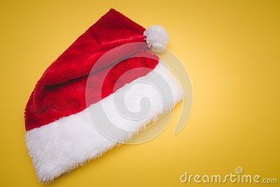 Christmas red Santa Claus hat with white pompom yellow . Decoration background