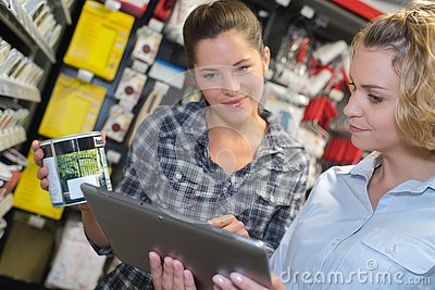 Woman choosing color paint during hardware shopping in home improvement