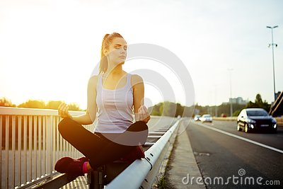 Woman relaxing next to a busy road, challenge concept