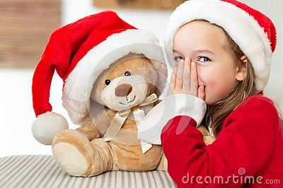 Cute young girl wearing santa hat whispering a secret to her teddy bear christmas present toy. Cheeky kid with teddy bear.