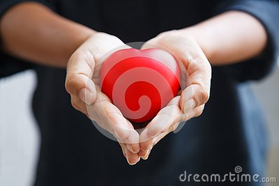 Red heart held by female`s both hands, represent helping hands, caring, love, sympathy, condolence, customer relationship, patient
