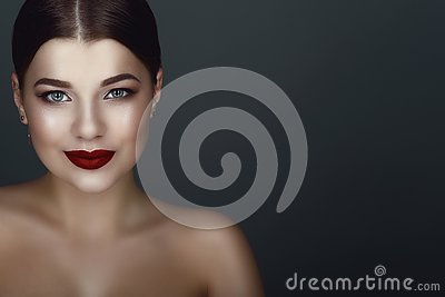 Close up portrait of beautiful smiling dark-haired model with perfect make up and centre part sleek bun