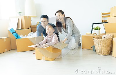 Happy young Asian family of three having fun moving with cardboard boxes in new house at moving day. Moving house day and express