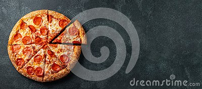 Tasty pepperoni pizza and cooking ingredients tomatoes basil on black concrete background. Top view of hot pepperoni pizza. With