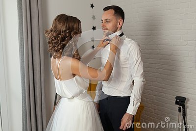The bride and groom in the morning at the hotel on a wedding day. Dressing a newly-married couple Woman help fixing bowtie to