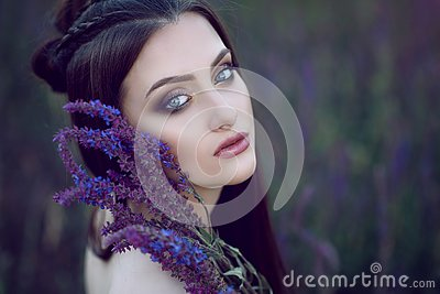 Beautiful blue-eyed lady with perfect make up and plaited hairstyle sitting in the field and holding purple flowers at her face