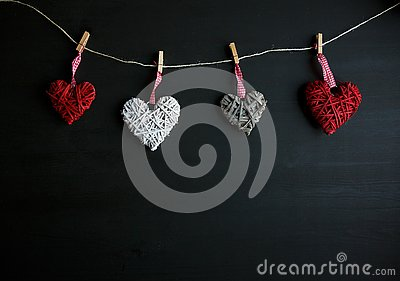 Four white and red hearts on black wooden table. Valentines, spring background. Mock up with copyspace. happy mothers day