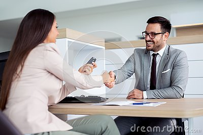 Happy car dealer and customer shake hands after successfully signed contract.