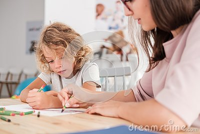 Child with an autism spectrum disorder and the therapist by a table drawing with crayons during a sensory