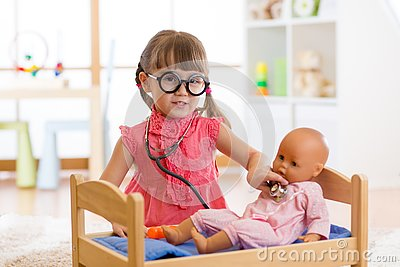Child in kindergarten. Kid in nursery school. Little girl preschooler playing doctor with doll.