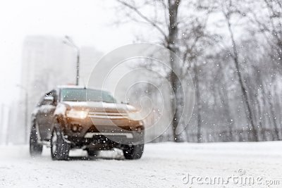 Heavy snowfall and blurred SUV awd car on road. 4wd vehicle on city street at winter. Seasonal roadside assistance concept.