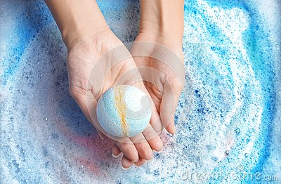 Woman holding color bath bomb over foam