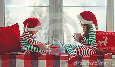 Children girl and boy in pajamas is sad on Christmas morning by window