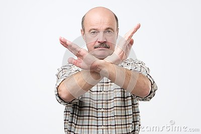 Senior bald man with mustache making stop sign with hand. I do not give you a permission.