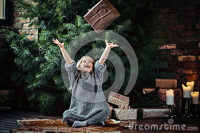 Joyful little girl with blonde curly hair wearing a warm sweater throws up a gift box while sitting on a floor next to