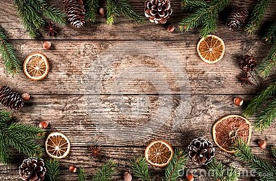Creative layout frame made of Christmas fir branches, spruce, slices of orange, pine cones, snowflakes on wooden background
