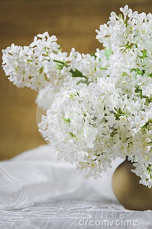 A bouquet of white lilac in a clay pot on a wooden background. Close-up, soft focus