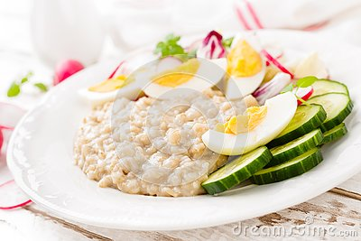 Oatmeal porridge with boiled egg and vegetable salad with fresh radish, cucumber and lettuce. Healthy dietary breakfast