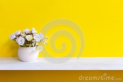 Yellow wall with white flower in vase on shelf white wood,