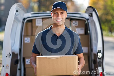 Smiling delivery man standing in front of his van holding a package