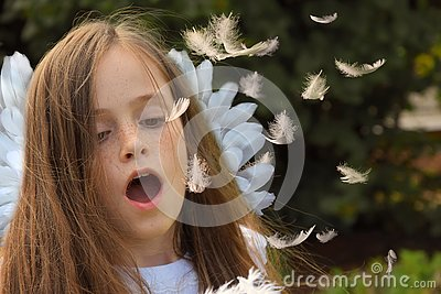 Teenage girl in angel costume blows flying feathers