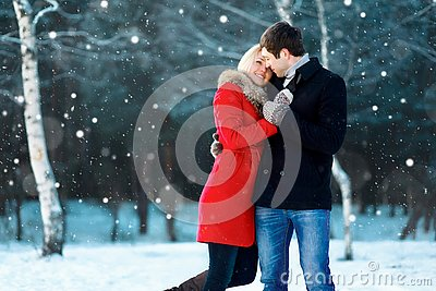 Happy romantic young couple walking in winter park on flying snowflakes snowy