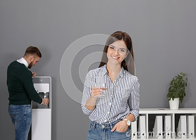 Young woman with glass of water near cooler