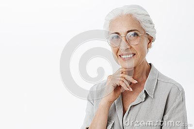 Waist-up shot of wise and pleased carefree kind grandmother in glasses with white hair holding hand on chin in