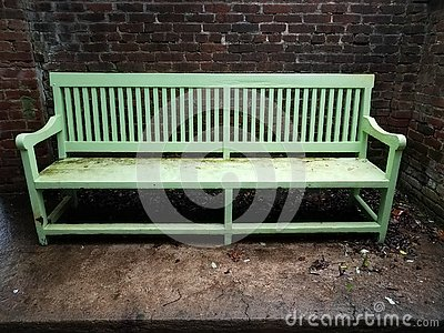 Wet green bench with red brick wall