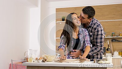 Young wife giving affection to her husband while cooking