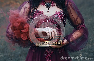 Legend of Pandora`s box, girl with black hair, dressed in a purple luxurious gorgeous dress, an antique casket opened