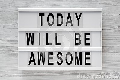 `Today will be awesome` words on lightbox over white wooden surface, top view.