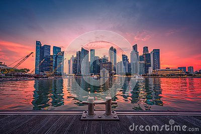 Singapore Skyline and view of business district downtown with wooden walkway on Marina Bay at sunset.