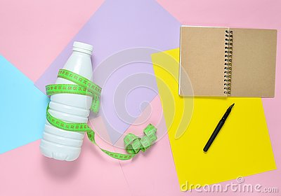 Notepad for compiling diet plan, bottle of kefir wrapped with ruler on colored paper background.