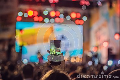 Use advanced mobile recording, fun concerts and beautiful lighting, Candid image of crowd at rock concert, Close up of