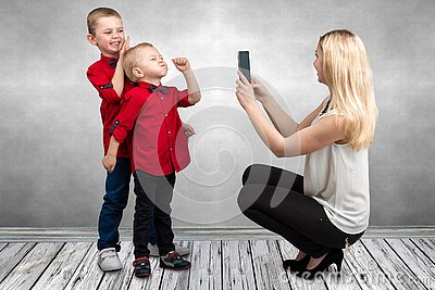 Mom takes on mobile phone two sons.Children play fun and indulge.Fun leisure.