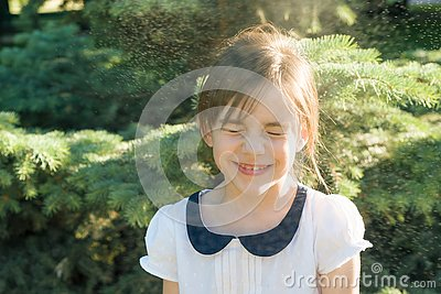 Happy little girl with closed eyes in spray of thermal water drops on hot summer day in the park