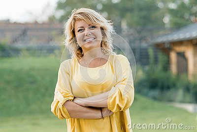 Outdoor portrait of positive confident mature woman. Smiling female blonde in a yellow dress with arms crossed near the house