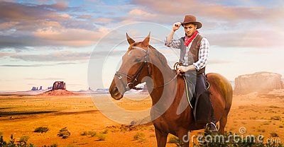 Cowboy riding a horse in desert valley, western