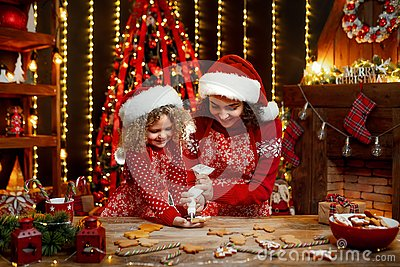Merry Christmas and Happy Holidays. Cheerful cute curly little girl and her older sister in santas hats cooking