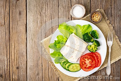 Steamed cod fish. Paleo, keto, fodmap healthy diet with vegetables on white plate on white table, side view.