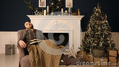 stock image of young man sleeping in a chair on christmas evening. boring christmas concept.