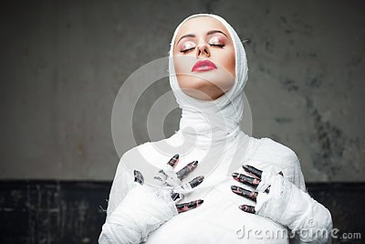 Glamorous mummy. Portrait of a young beautiful woman in bandages all over her body