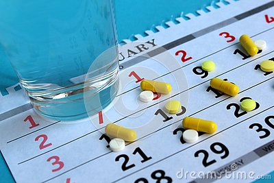 stock image of there is medicine on the calendar every day and there is a glass of water