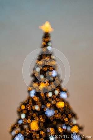 Bokeh; colorful Christmas tree shimmering against the background of the evening pastel sky