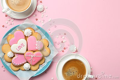 Romantic breakfast with heart shaped cookies and cups of coffee on color background