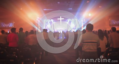 Christmas concept: Blurred Christian Congregation Worship God together in Church hall in front of music stage and light effected